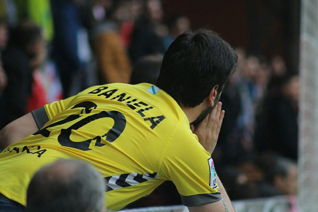 Dani Baniela gritando con su camiseta amarilla del CD Lugo con en número 20 a la espalda.